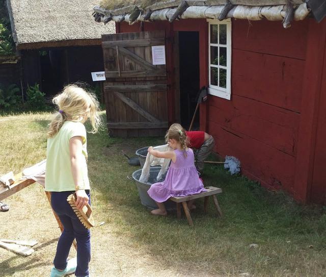 Två barn med långt hår fotograferade bakifrån när de interagerar med den kulturhistoriska miljön på Hallandsgården i Halmstad.