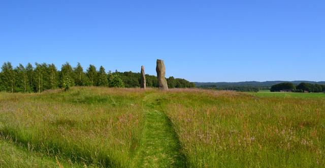 Asige vid Hagbards galge, uppresta stenar på en äng och blå himmel.