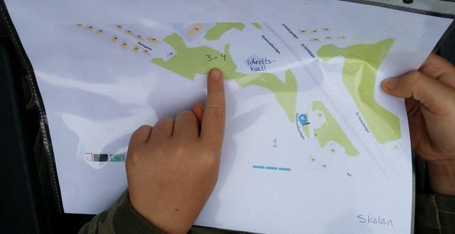 En barnhand pekar på ett kartblad som ligger i en plastficka.