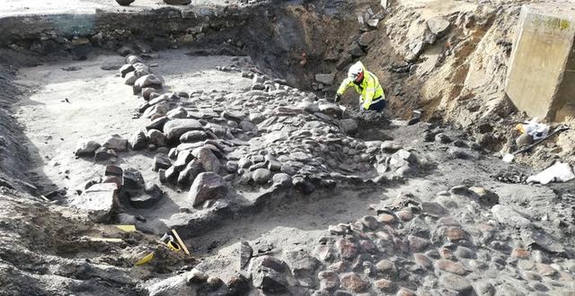 En arkeolog i skyddskläder står i en stor grop där stenläggning grävts fram.