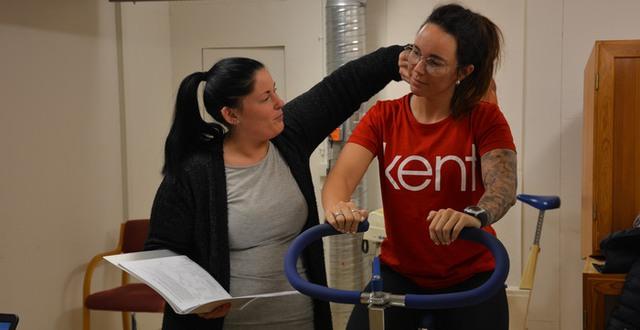 Två deltagare som studerar till Hälsovägledare tar pulsen efter cykling