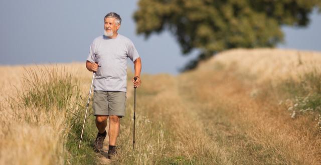 Äldre man promenerar med stavar