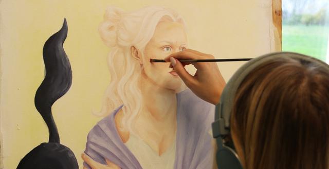 Tjej på bild- och konstlinjen målar ett porträtt i med utsikt över havet.