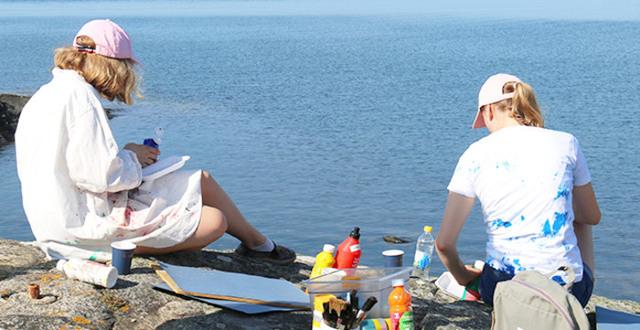 Flickor sitter och målar på en klippa med havet framför sig.