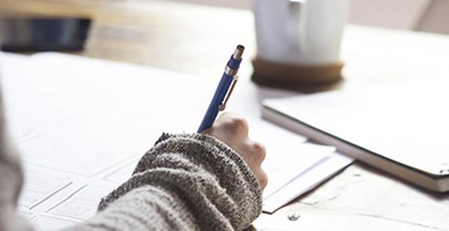 Hand med penna som skriver
