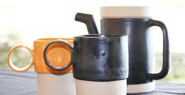 Muggar och kanna i orange och svart skapade av deltagare på Keramiklinjen på Löftadalens folkhögskola.
