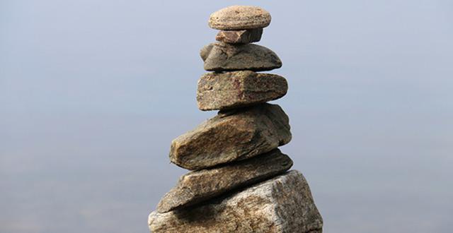 Stenar staplade som ett torn framför havet.